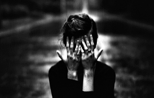 Black and white photo of a white cis woman with her head in her hands