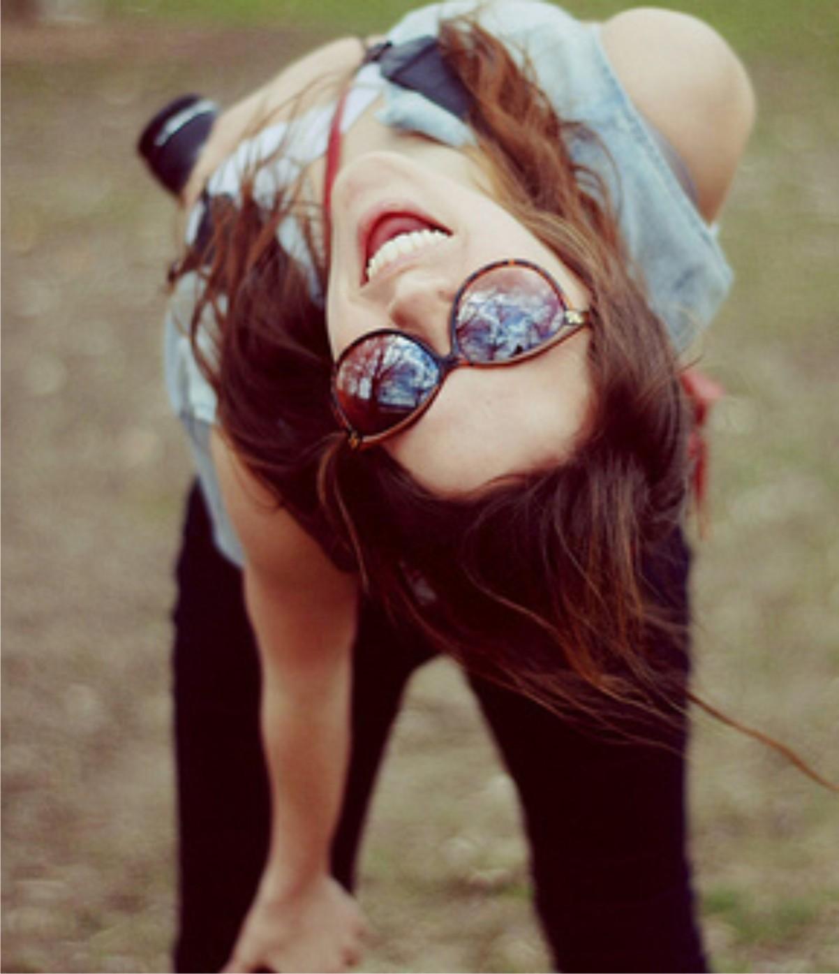 девушка в очках с фотоаппаратом в руках улыбается.