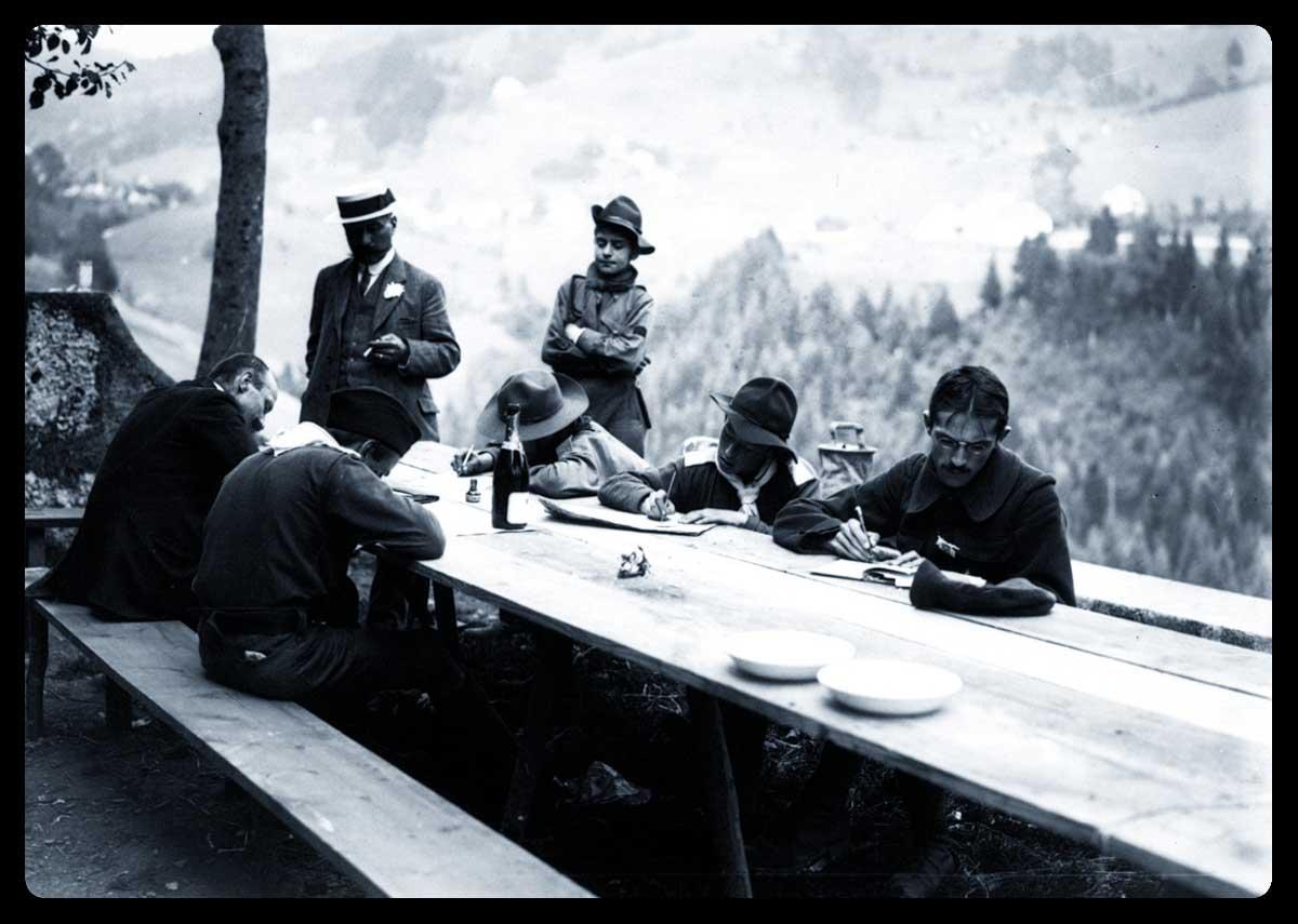 Boys scouts écrivant dans les environs de Grenoble, en 1913, assis autour d'une table - Source : Gallica.bnf.fr