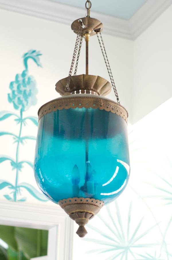 Blue lantern pendant in an aqua and white beach house.