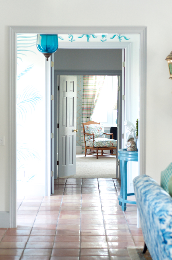 Pool blue and white beach house entry, with terracotta floors and hand-painted mural.